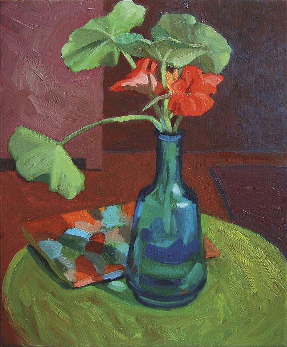 Table ronde verte avec vase bleu et capucines