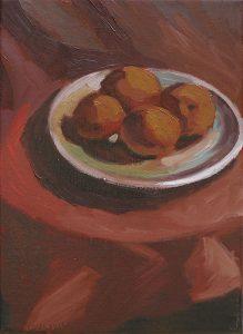 assiette d'abricots sur une table avec une nappe rouge