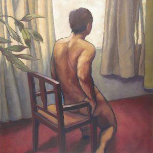 homme nu assis sur un fauteuil devant une fenêtre avec des rideaux gris