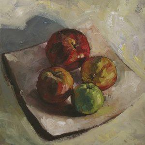 4 pommes rouges jaune et vert sur une coupe blanche